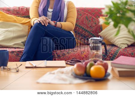 Cropped image of woman sitting on sofa in her roo