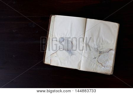 Open old vintage book on dark wood background. Historical and memorable concept.