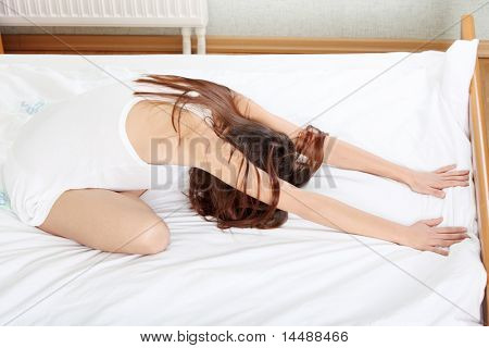 Beautiful brunette woman on bed practicing yoga