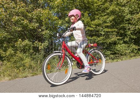 Adorable kid girl with pink helmet riding a bicycle