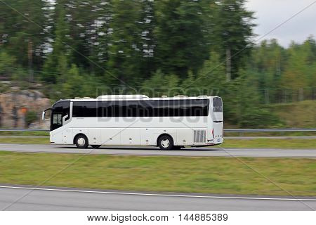 PAIMIO, FINLAND - AUGUST 26, 2016: White Chinese ZhongTongBus luxury coach at high speed on motorway in South of Finland. In-camera motion blur.