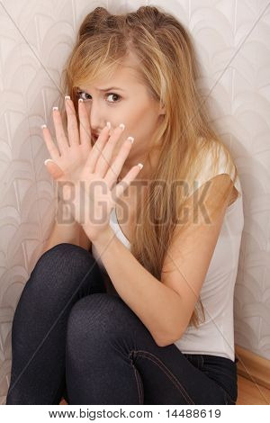 Abused young woman trying to hide and defend herself