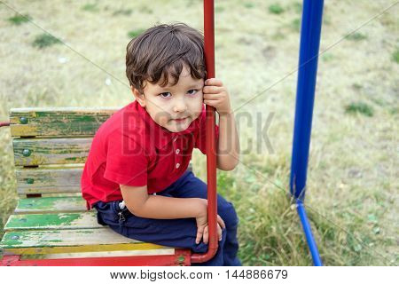 little boy riding on a swing outdoors