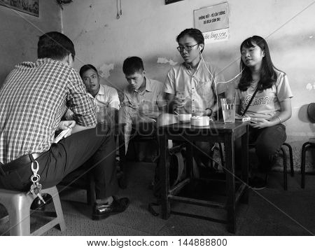 Hanoi, Vietnam - Aug 29, 2016: Young Asian people drinking coffee at an old and low price coffee shop on Hanoi old quarter street.