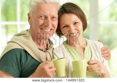 Happy senior father with daughter at home with tea