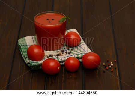Tomato juice and spices on a dark background