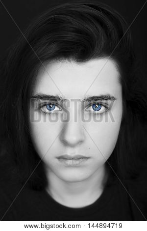 A portrait of a handsome blue eyes teenager on dark background. Monochrome