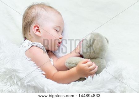 Portrait of a cute sleeping baby girl in bed