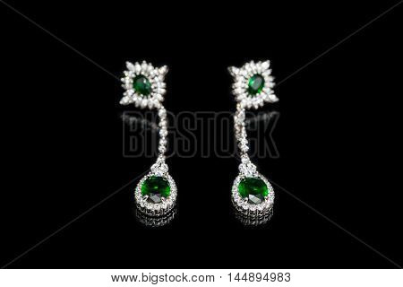 Earrings with green stones isolated on black glass, close-up