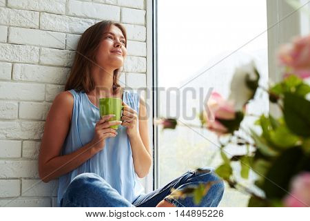 A charming young girl is very pleased while dreaming about something sitting on the window-sill and drinking a cup of aroma coffee