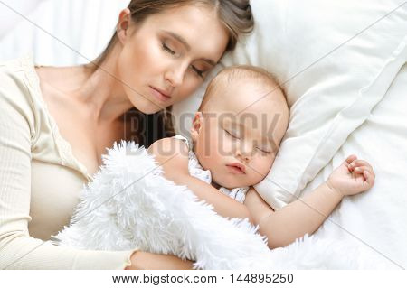 Sleeping mother and cute child in bed