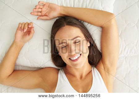 Top view of beautiful young woman holding hands behind head while sleeping and in bed
