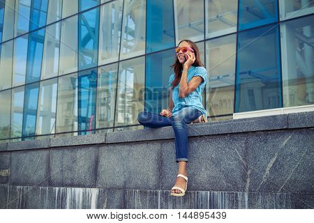 Caucasian girl in cheerful mood is talking on smart phone while sitting on the concrete bench in the downtown