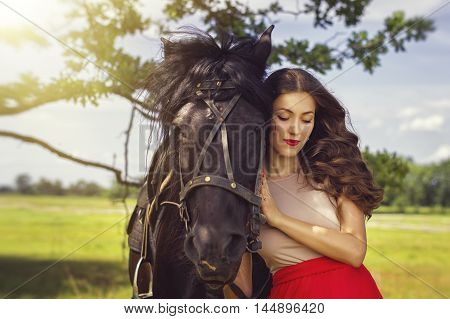 Portrait of a young woman with shut eyes standing near a black horse in the park. Focus on a person.