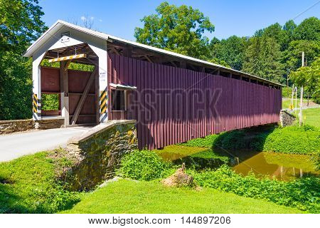 Kirkwood PA - August 23 2016: The White Rock Covered Bridge spans the West Branch of the Octoraro Creek in southeast Lancaster County. The single span wooden burr bridge is 103 feet long.