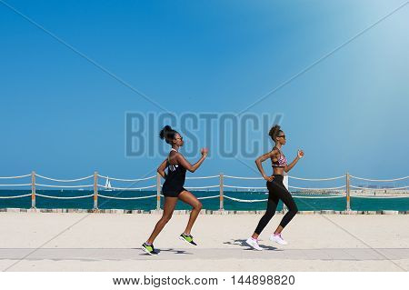 Two african females jogging along Dubai beach in United Arab Emirates