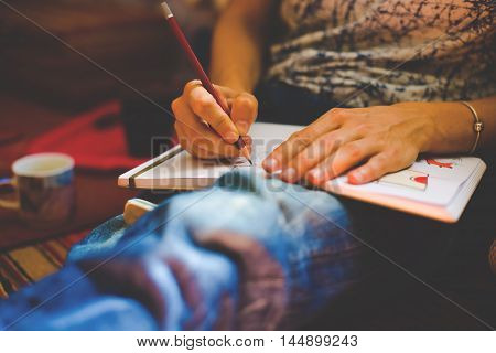 A Person Draws With A Pencil In A Notebook.
