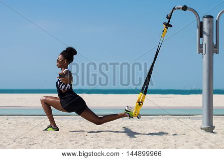 Female african athlete balancing with the help of suspension trainer. Outdoor sport activity