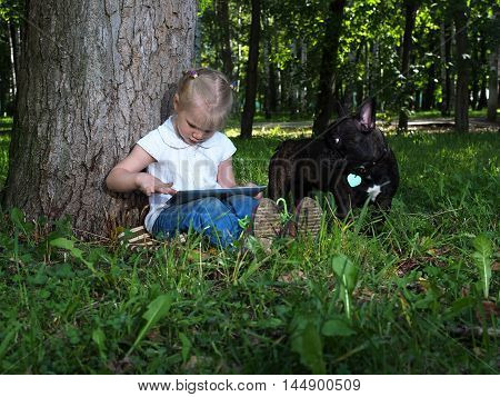 Little girl sitting alone in the park with tablet computer. Green grass summer. Dog black French bulldog