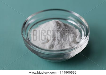 Baking soda, Sodium bicarbonate in glass bowl on wooden table.