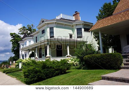 PETOSKEY, MICHIGAN / UNITED STATES - AUGUST 5, 2016: An elegant Victorian mansion with a wraparound porch on Division Street near downtown Petoskey, Michigan.