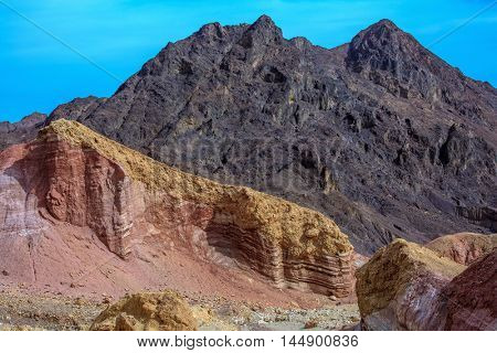 Black basalt mountains of King Solomon. Multi-colored mountain of Eilat, Israel. Warm January day