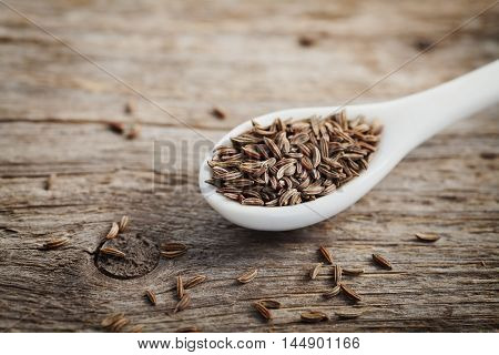 Cumin seeds or caraway in white spoon on wooden board. Rustic style. Organic spice.