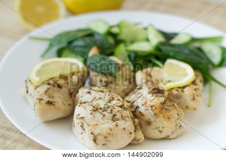 Freshly cooked white chicken meat served with thyme lemon and green salad