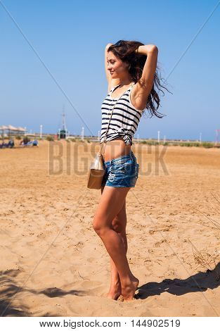Beautiful Strong Enjoying Woman Posing On The Beach In Blue Shorts With Fashion Bag