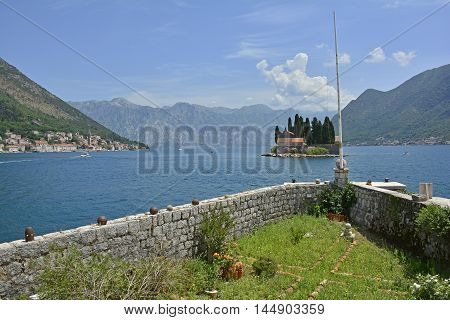 The tiny St George's Island in Kotor Bay Montenegro also known as the Island of the Dead. The island contains a 12th century Benedictine abbey and a cemetery. The village of Perast can be seen on the coast in the background and part of the island of Our L
