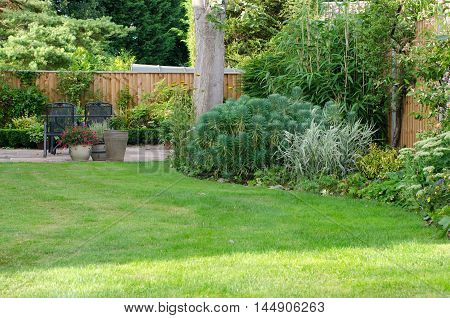 Garden with patio area lawn and flowerbeds.
