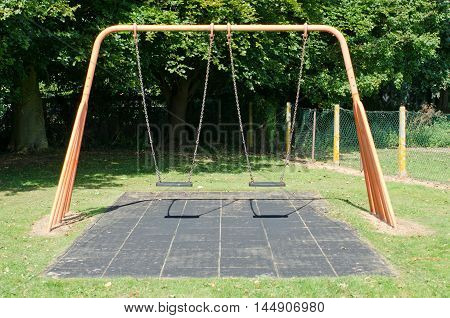 Empty swings in a playground on a sunny day