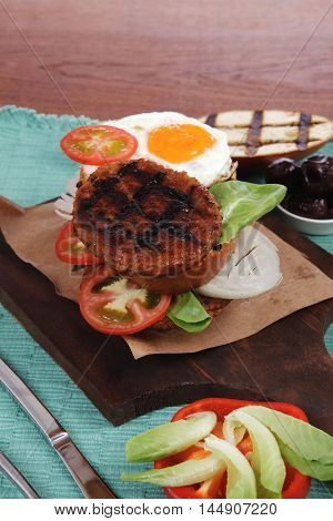 junk food big beef hamburger fried eggs on dark wood plate with modern cutlery ketchup sauce and pickles on blue mat isolated over white background