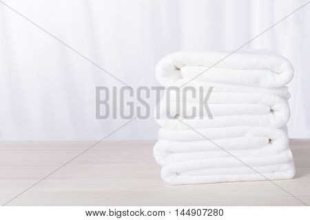 Stacked white plush spa hotel towels on table