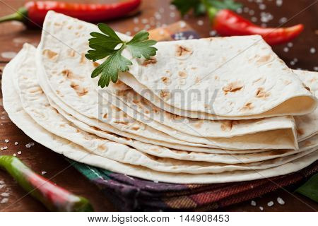 Mexican flatbread tortilla in plate on wooden table, top view.
