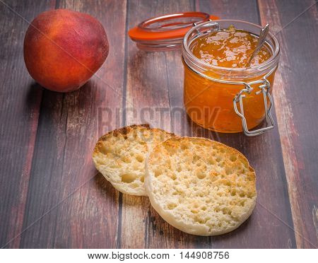 Peach jam / jelly in a jar with an English muffin on wood surface.