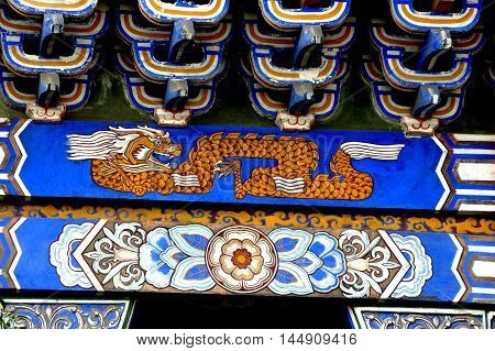 Dan Jing Shan China - November 16 2012: Hand-painted dragon and floral designs decorate the great hall of the Fo Shan Gu Xi Buddhist Temple