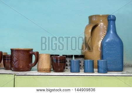 Bunch of various looking retro ceramic crockery on a top of a kitchen shelf front indoor shot
