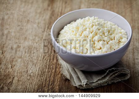 Cottage cheese or curd in bowl on rustic table, rural style. Copy space for your text.