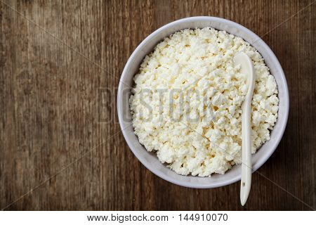 Cottage cheese or curd in bowl on rustic table, rural style, top view.