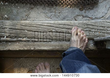 Male bare feet stepping out of the house overhead indoor shot