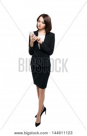 Beautiful business woman in elegant black dress typing on her smartphone. Full body length portrait isolated over white studio background.