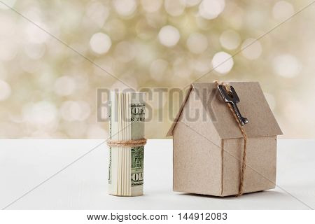 Model of cardboard house with key and dollar bills. House building, loan, real estate, insurance, rent, investment, construction or cost of housing or buying a new home concept.