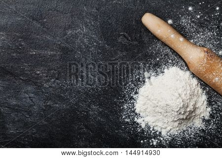 Baking desk with flour and rolling pin, top view. Space for text.