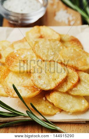 Homemade potato chips with sea salt and herb on wooden cutting board.