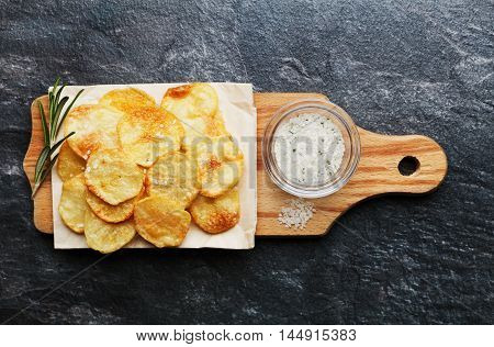 Homemade potato chips with sea salt and herb on wooden cutting board, top view.