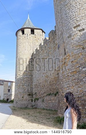 Tourist girl seeing a tower of Carcassonne city in France