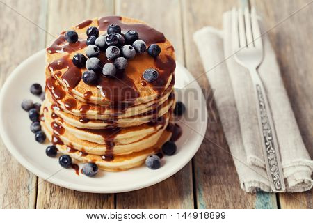 American pancakes or fritters with chocolate sauce and frozen blueberries in a white plate on a wooden rustic table. Delicious dessert for breakfast.