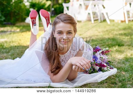 bride lying on the grass in the spring garden.