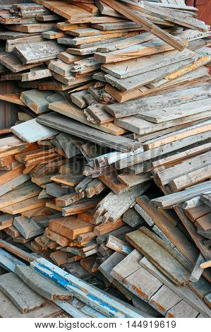 Firewood background - chopped firewood of obsolete wooden construction parts on a stack